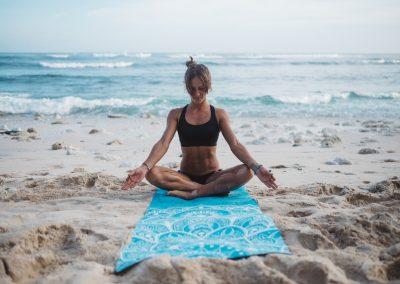 jógová podložka Mandala Turquoise na pláži s jogínkou