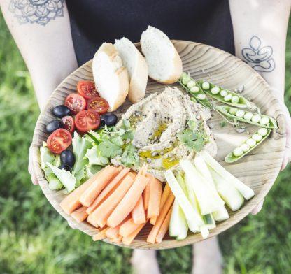 přírodní talíř z teakového dřeva velký s chlebem a zeleninou v dlaních