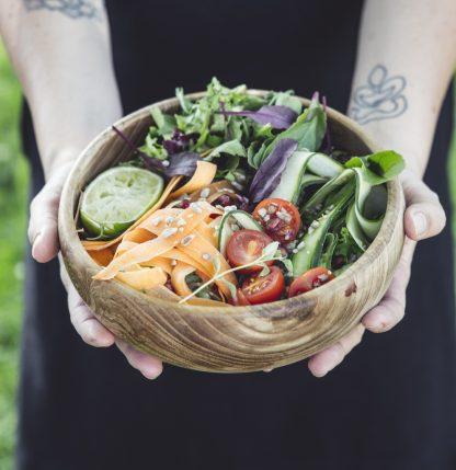 přírodní mísa z teakového dřeva na salát se zeleninovým salátem v dlaních
