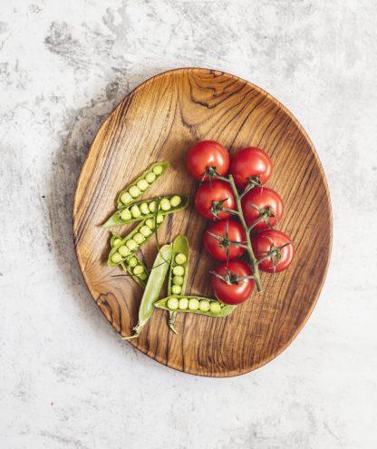 přírodní oválný talíř z teakového dřeva s rajčaty a hráškem